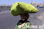 Caption: Modern Culture; Egyptian woman carrying large sack on her head down the street from the grand mosque